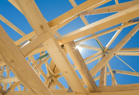 roof framing: New residential construction home framing against a blue sky