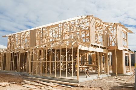 studs: New residential construction home framing against a blue sky.