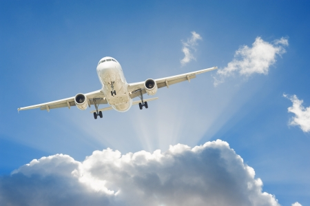 airplane landing: Large passenger airplane flying in the blue sky