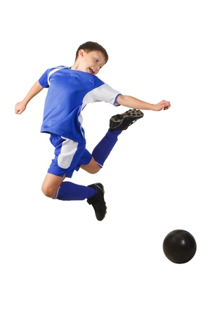 soccer kick: A young boy football player in blue uniform isolated on white