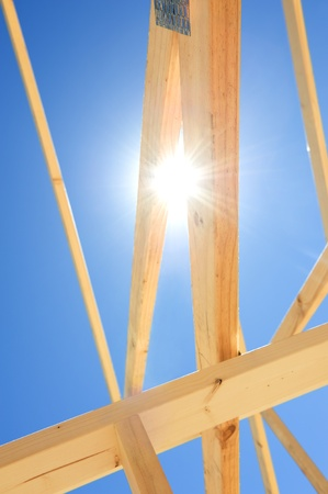 Fragment of a new residential construction home framing against a blue sky photo