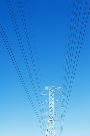 isolator high voltage: High voltage power pole against blue sky Stock Photo