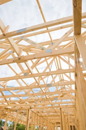 roof framing: New residential construction home wooden framing against a blue sky Editorial