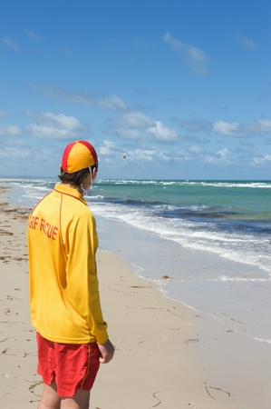 young man  life saver  watching the situation on the sea photo