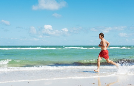 muscular young man running along the coast photo
