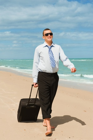 business trip: Businessman walking on the beach the first day of vacation