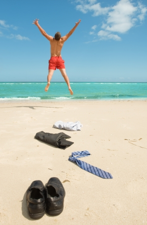 jumping businessman: young businessman jumping on the beach after a big deal