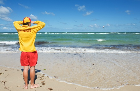 emergency vest: young man  life saver  watching the situation on the sea