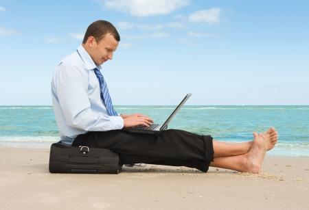 jornada de trabajo: hombre de negocios joven que trabaja con la computadora portátil en la playa