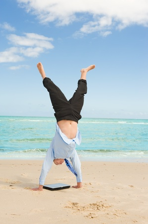 young businessman doing handstand on the beach after a big deal photo
