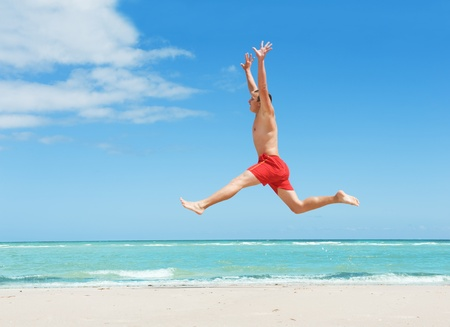 muscular young man jumping on the beach  photo