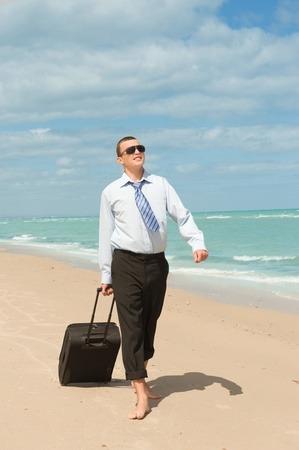 Businessman walking on the beach the first day of vacation photo