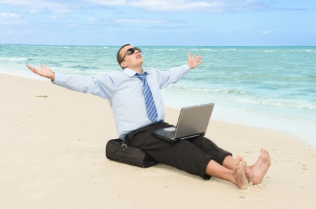 barefoot man: young businessman working with laptop on the beach  Stock Photo
