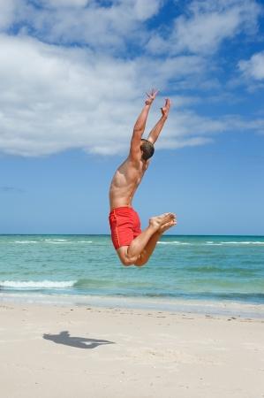 ビーチでジャンプ筋肉の若い男
