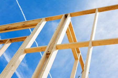 Fragment of a new residential construction home framing against a blue sky Stock Photo - 13235459
