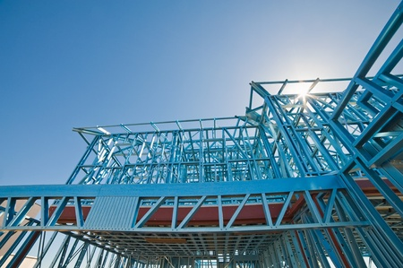 晴れた空に対して鋼鉄フレームを使用して建設中の新しい家