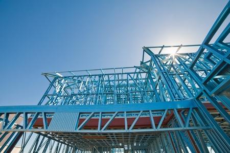 Nieuw huis in aanbouw met behulp van stalen frames tegen een zonnige hemel Stockfoto