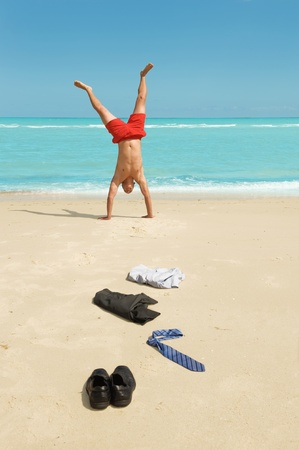 emotional freedom: young businessman doing handstand on the beach after a big deal