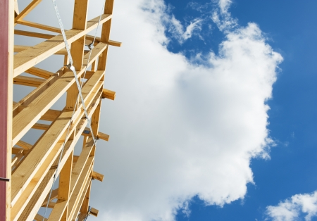 Fragment of a new residential construction home framing against a blue sky. Stock Photo - 13832743