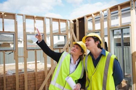 ingeniero civil: ingeniero civil y los trabajadores discutir temas en el sitio de la construcción