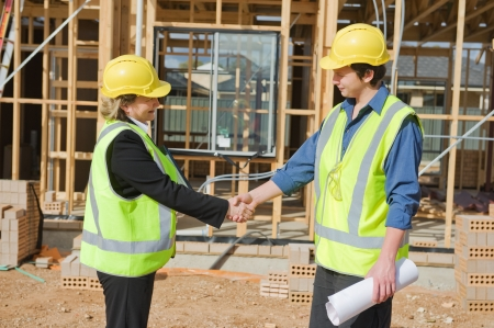civil: civil engineer and worker shaking hands at the construction site