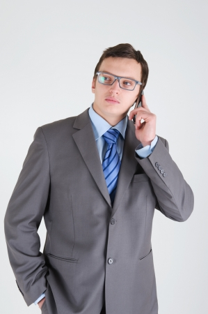 moneymaker: Young businessman with mobile phone wearing glasses