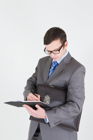 moneymaker: Portrait of handsome young businessman with notebook and briefcase