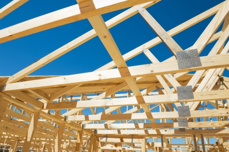 building material: New residential construction home framing against a blue sky