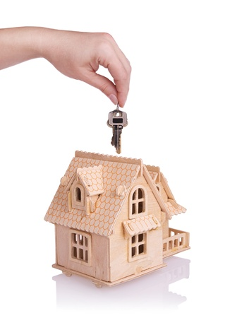 Conceptual image with small house and keys.Isolated on white photo