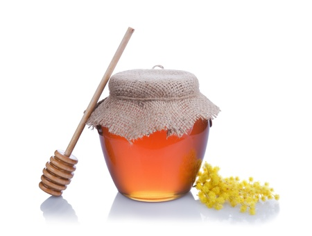 Honey with wood stick and flowers isolated on white background photo
