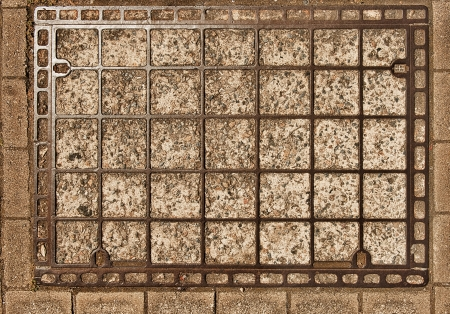 Old rectangular manhole cover as a grunge background photo