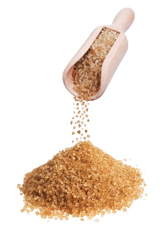 unrefined: heap of brown sugar and wooden scoop on white background