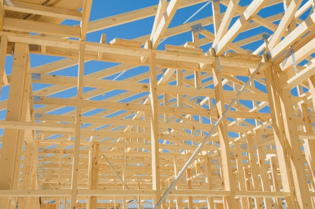 joists: New residential construction home framing against a blue sky.