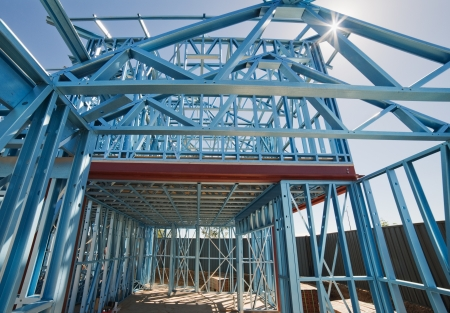 roof framing: New home under construction using steel frames against a sunny sky.