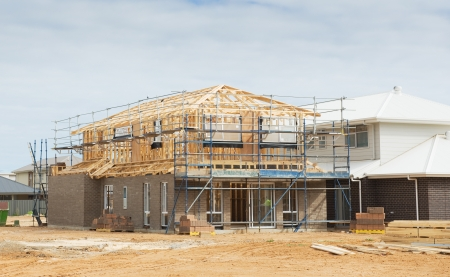 new site: Construction site with the house in scaffolding against a blue sky
