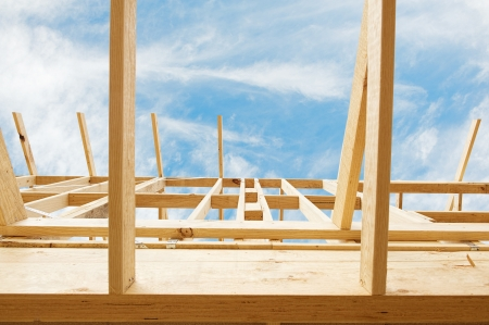 wooden joists: New residential construction home framing against a blue sky.Shallow focus.