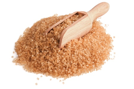 heap of brown sugar and wooden scoop on white background photo