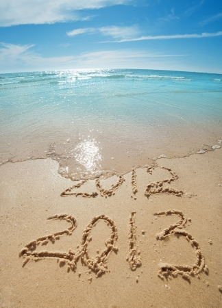 digits  2012 and 2013 on the sand seashore - concept of new year photo