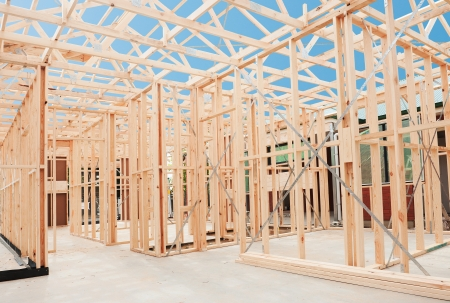 residential structures: New residential construction home framing against a blue sky