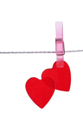 two red hearts pinned together isolated on white background photo