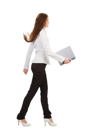 young businesswoman walking with laptop, isolated on white background Stock Photo - 17591704