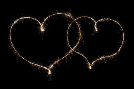 two hearts from sparkler isolated on black background photo