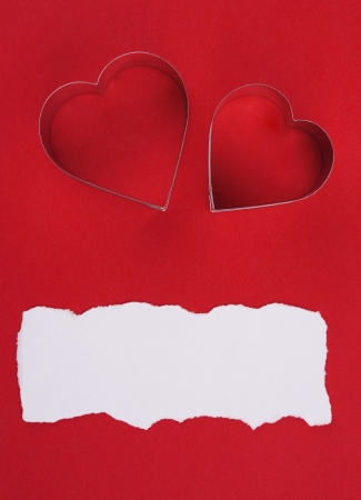 two metal hearts shaped over red background photo