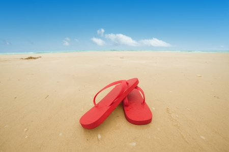 Red flip flops on the beach sand Concept of summer vacations photo