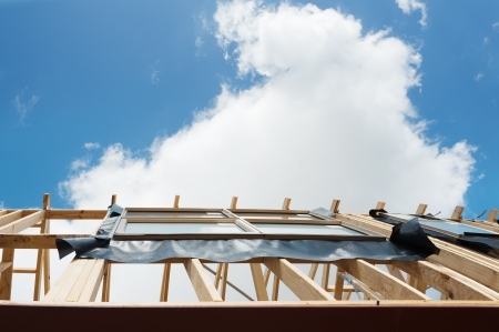 Fragment of a new residential construction home framing against a blue sky. Stock Photo - 18621130