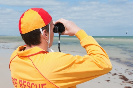 eye protectors: young man  life saver  watching the situation on the sea