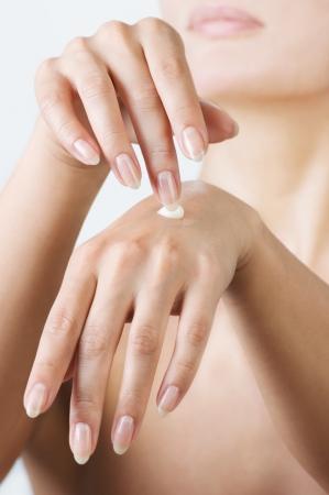 Woman hands applying moisturizing cream to her skin.Shallow\ focus