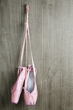 ballet slipper: Old used pink ballet shoes hanging on wooden background