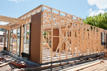 wooden joists: New residential construction home framing against a blue sky