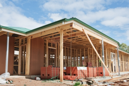 TRUSS: New residential construction home framing against a blue sky